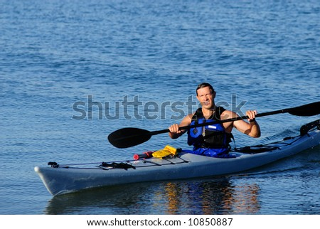 Kayaker arrives from exercises in calm blue waters of Mission Bay, San Diego, California - stock photo
