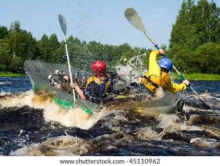 Kayaker extreme sporting a kayak cuts through water - stock photo