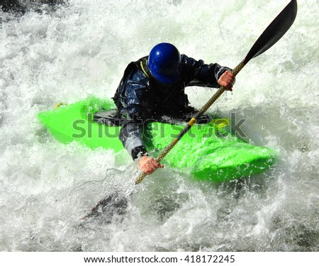 Kayaker is surrounded by white water on a river in Tennessee.  Kayak is green and his helmet is blue. - stock photo