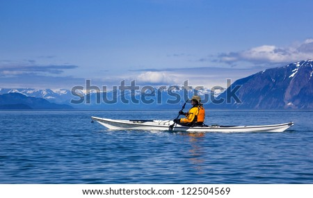 Kayaker paddling in Glacier Bay National Park with mountains on the background - stock photo