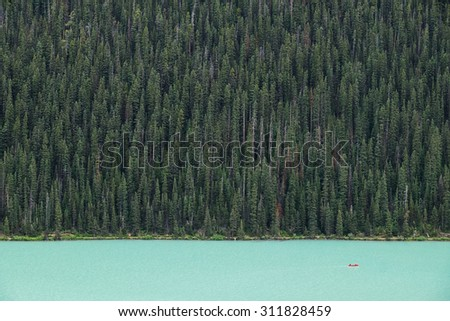Kayakers on Lake Louise backdropped by a forest of giant fir trees in Banff National Park, Canada. - stock photo