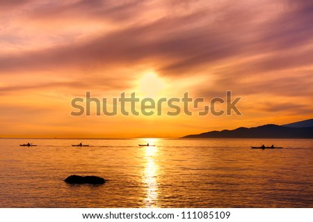 Kayakers silhouette on ocean during orange sunset was taken off the shores of Vancouver, British Columbia, Canada - stock photo