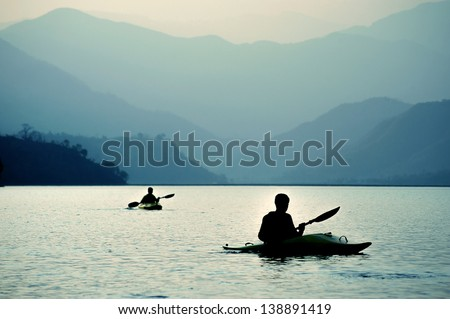 Kayaking at sunset in the mountains - stock photo