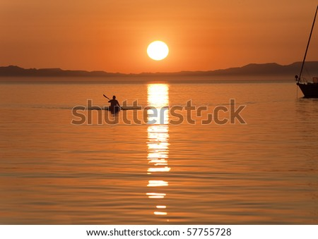 Kayaking in Sea of Cortes, Baja Mexico, at sunset - stock photo
