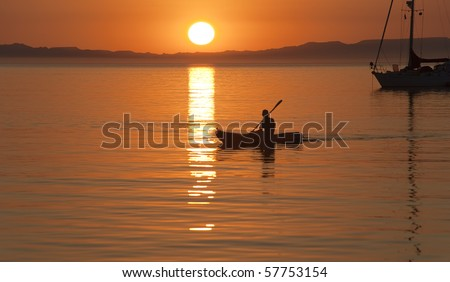 Kayaking in Sea of Cortez with sailboat in  background, at sunset - stock photo