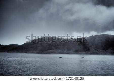 Kayaking in the fog on the Russian River. This image exemplifies peace, quiet and solitude. - stock photo