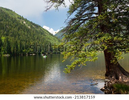 Kayaking on Cottonwood lake in the valley on clear calm day with the lake stretching off to distance - stock photo