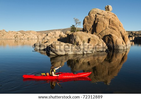 Kayaking on Quiet Lake with Boulders and Rocks - stock photo