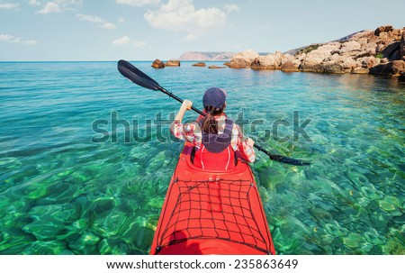 Kayaking. The woman floating on the sea kayak. Leisure activities on the sea. Canoeing. - stock photo