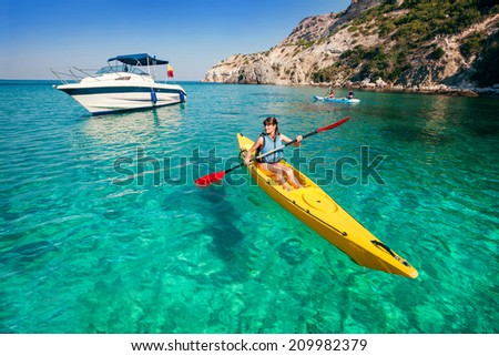 Kayaking. Travel adventure kayak on the tropical sea on a sunny day. Woman rowing a canoe. - stock photo