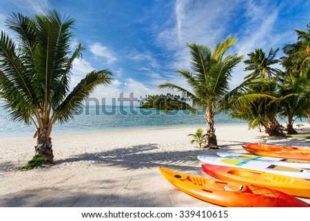 Kayaks at beautiful tropical beach with palm trees, white sand, turquoise ocean water and blue sky at Cook Islands, South Pacific
