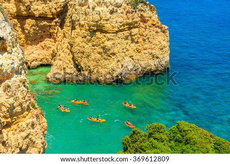 Kayaks in sea bay on turquoise sea water on coast of Portugal - stock photo