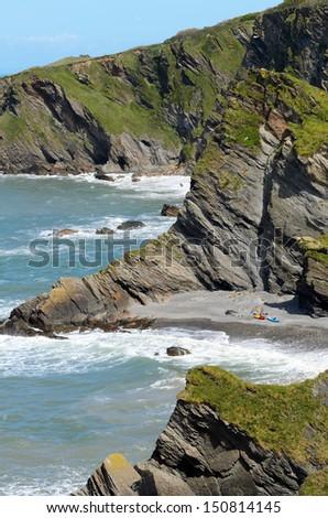 Kayaks on beach in Hele Bay near the village of Illfracombe in North Devon England - stock photo