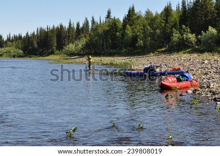 Kayaks on the beach. Tourist boats are coast North of the Ural river. - stock photo