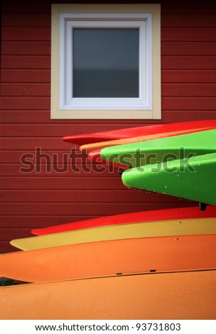 Kayaks stacked on their sides in the rain. - stock photo