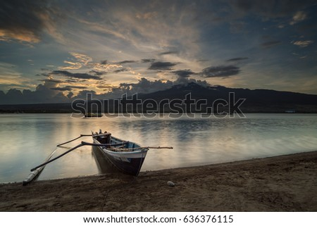 Kayangan beach, East Lombok, Indonesia - April 22, 2017 : Fishing boat left behind on the beach during sunset