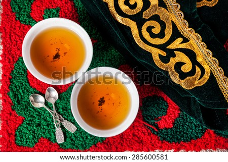 Kazakh national hat and black tea in two teabowls on the ethnic red carpet with oriental green pattern  - stock photo