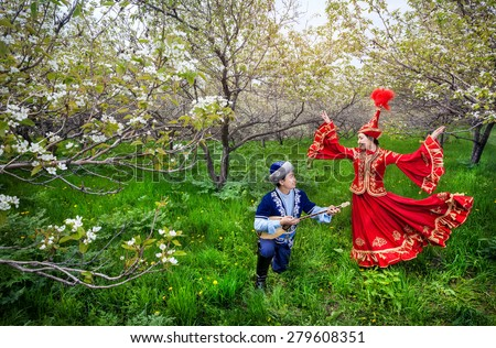 Kazakh woman dancing in red dress and man playing dombra at Spring Blooming garden in Almaty, Kazakhstan, Central Asia - stock photo