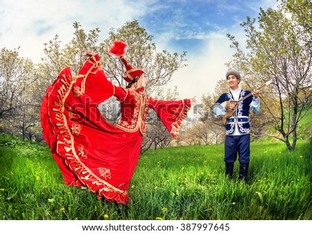 Kazakh woman dancing in red dress and man playing dombra at Spring Blooming garden in Almaty, Kazakhstan, Central Asia
