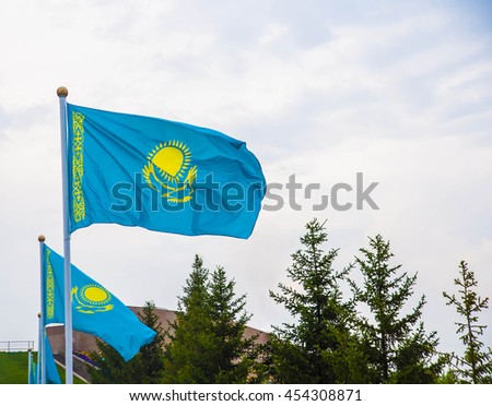 Kazakhstan flag waving on the wind against blue sky with clouds.  - stock photo