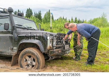 KAZOVO, ARKHANGELSKY REGION/RUSSIA - JUNE 23: Two men switch on winch of Land Rover Defender SVX 60-year special edition vehicle sunk in mud against forest background on June 23, 2010 in Kazovo.  - stock photo