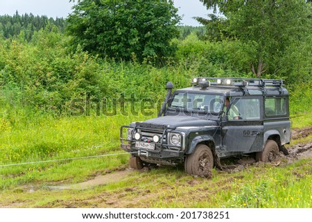 KAZOVO, ARKHANGELSKY REGION/RUSSIA - JUNE 23: Winching of Land Rover Defender SVX 60-year special edition vehicle sunk in mud on June 23, 2010 in Kazovo.  - stock photo