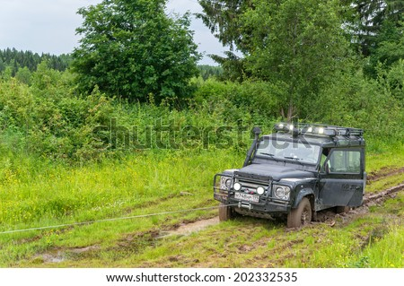 KAZOVO, ARKHANGELSKY REGION/RUSSIA - JUNE 23: Winching of Land Rover Defender SVX 60-year special edition vehicle sunk in mud on June 23, 2010 in Kazovo.