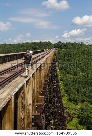 KEATING, PENNSYLVANIA,USA-JULY 15: Visitors walk on the remains of the Kinzua viaduct on July 15, 2013. The rail bridge collapsed in 2003 due to a tornado and is now a tourist walkway and state park. - stock photo