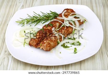 Kebab barbecue with rosemary and onion rings on the wood background - stock photo