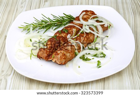 Kebab barbecue with rosemary and onion rings on the wood background