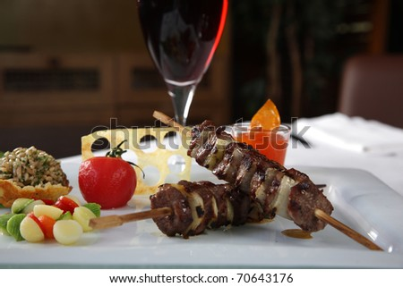 Kebab on a white dish with a glass of wine and vegetables - stock photo