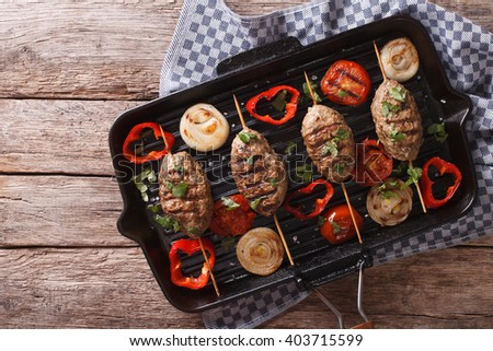 kebab with grilled vegetables on the grill pan on the table. horizontal view from above