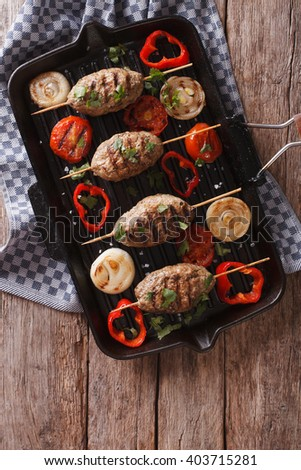 kebab with grilled vegetables on the grill pan on the table. vertical view from above
