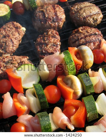 Kebabs and burgers cooking on a barbeque - stock photo
