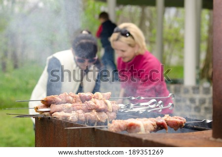 Kebabs ready for cooking standing piled on the grill on an outdoor BBQ as two women continue to prepare more food in the background, focus to the kebabs - stock photo