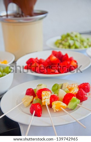 Kebabs with pieces of strawberry, mandarin and kiwi , fruit skewers - stock photo