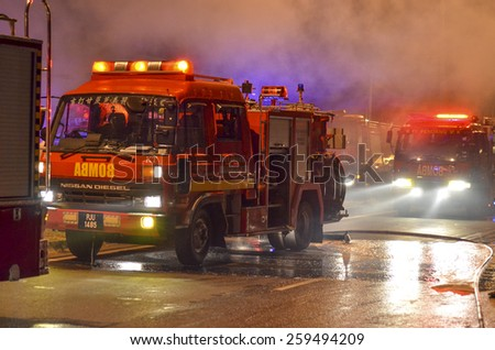 Kedah, Malaysia - March 8, 2015 : A supermarket was burned terribly and almost 10 Fireman vehicles come to rescue and stop the fire. The water was supplied from one kilometer away by Fireman Hose.