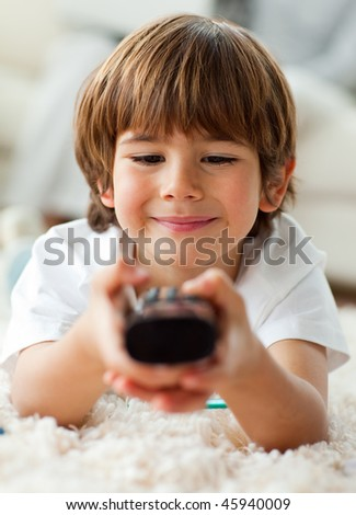 Keen little boy holding a remote lying on the floor in the living-room - stock photo