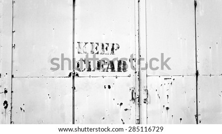 Keep Clear sigh on rusty metal door -  Black & White - stock photo