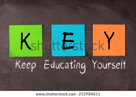 Keep Educating Yourself words with KEY notes on blackboard. - stock photo
