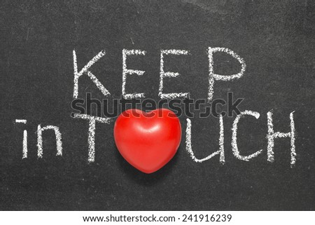 keep in touch phrase handwritten on blackboard with heart symbol instead of O