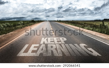 Keep Learning written on rural road - stock photo