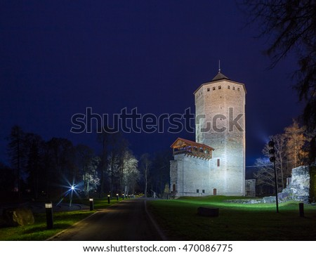 Keep - main tower of Paide castle in Estonia. Green park at ruins of castle. Night illuminated view.