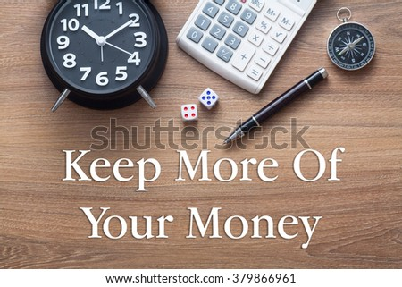 Keep more of your money written on wooden table with clock,dice,calculator pen and compass - stock photo