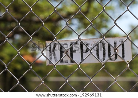 Keep Out sign on a chain link fence outside with tree and blue sky in background