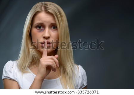 Keep silence. Close up of frustrated beaten young girl holding finger near mouth while expressing fear - stock photo