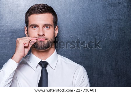 Keep silence! Handsome young man in formalwear showing a sign of closing mouth and looking at camera while standing against blackboard - stock photo