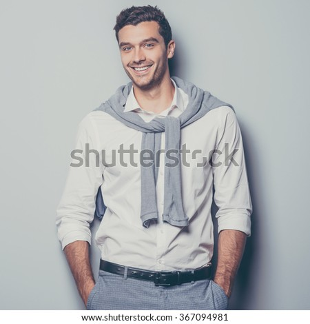 Keep smiling. Confident young man keeping hands in pockets and smiling while standing against grey background - stock photo