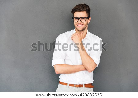 Keep smiling! Young handsome man keeping hand on chin and looking at camera with smile while standing against grey background - stock photo