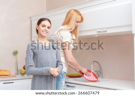 Keep the house clean. Cheerful smiling teen girl smiling at the camera while her mother washing dishes in a kitchen sink - stock photo